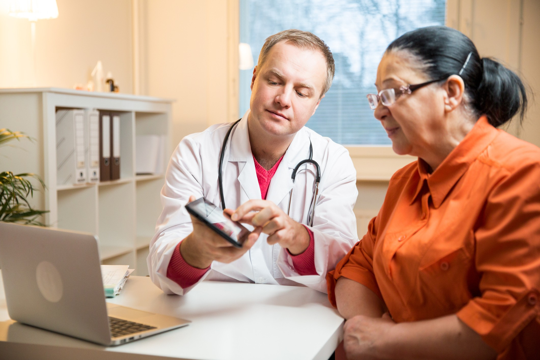 Smiling male doctor holding digital tablet, showing test results to patient in hospital. X-ray images on screen. Sick senior woman having a doctor appointment. Medical consultation.