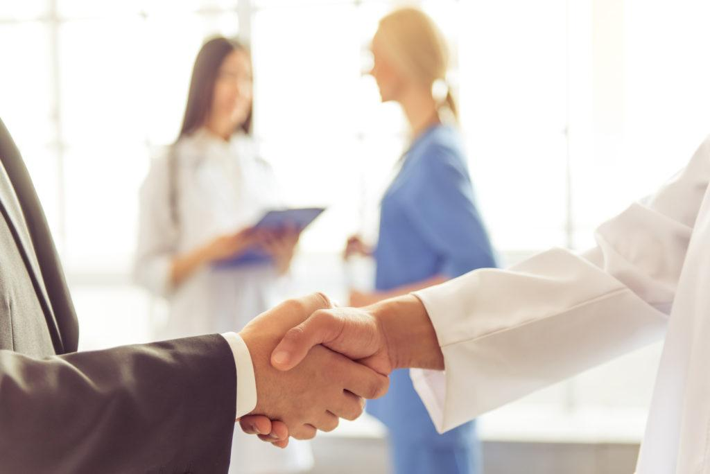 Cropped image of businessman and Afro American doctor shaking their hands, two female doctors are talking in the background