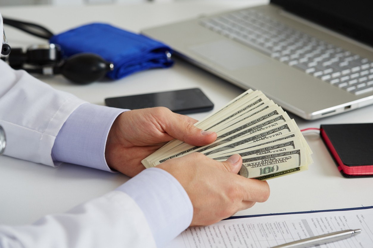 Male medicine doctor holding in hands bunch of hundred dollars banknotes counting them. Medic personnel salary, prestige and high paid job, education, public health business, medical insurance concept