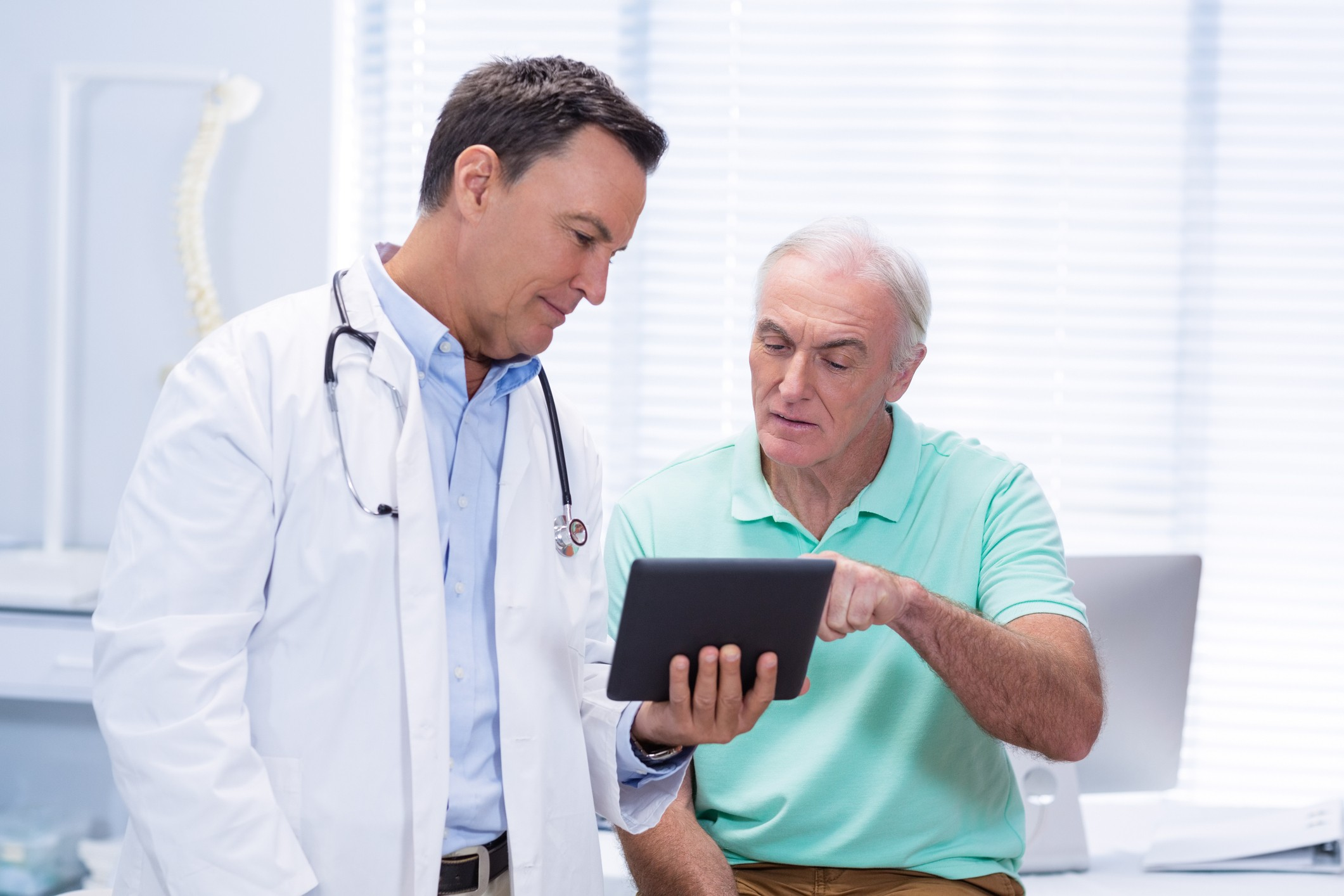 Doctor and senior patient using digital tablet in clinic