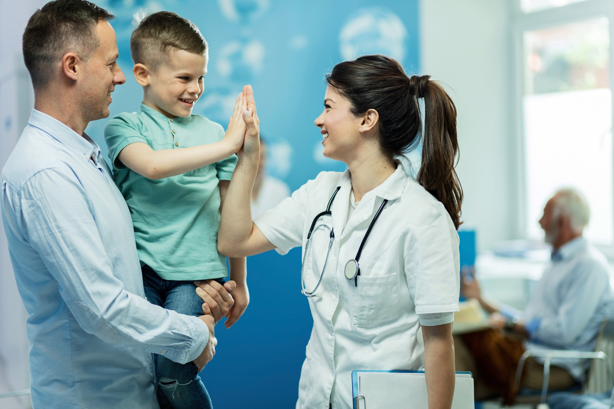 Happy female doctor giving high fie to a little boy who came with father at hospital.